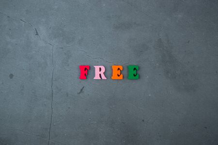 The multicolored free word is made of wooden letters on a grey plastered wall background Banque d'images - 128530194