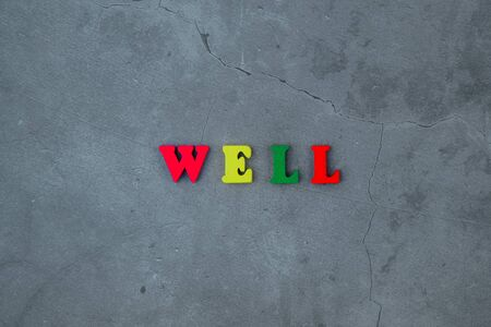 The multicolored well word is made of wooden letters on a grey plastered wall background Banque d'images - 128530207