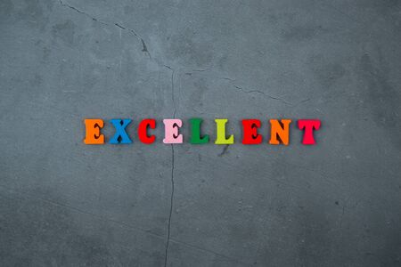 The multicolored excellent word is made of wooden letters on a grey plastered wall background. Banque d'images - 128530812