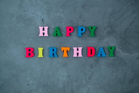 The multicolored happy birthday word is made of wooden letters on a grey plastered wall background. Banque d'images - 128530819