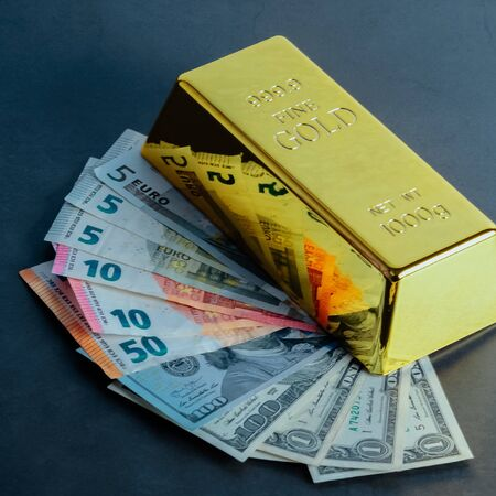Gold bar ingot bullion against the background of dollar and euro bills