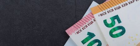 Euro bills. Different denominations on a gray background. 5, 10 50 euros