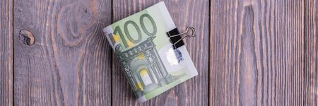 Euro cash banknotes on a dark wooden background