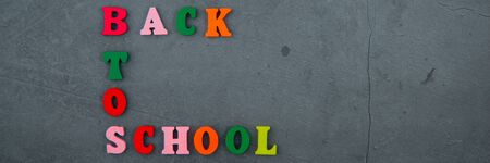 The multicolored back to school word is made of wooden letters on a grey plastered wall background Banque d'images - 129064081