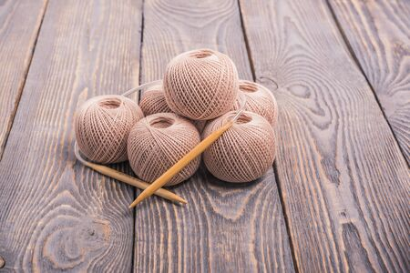 Balls of yarn and knitting needles for knitting on a wooden background