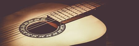 Acoustic guitar lying on a wooden table lit by a beam of light Banque d'images - 129064180