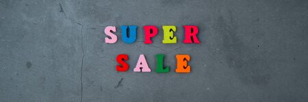 The multicolored super sale word is made of wooden letters on a grey plastered wall background Banque d'images - 129064257