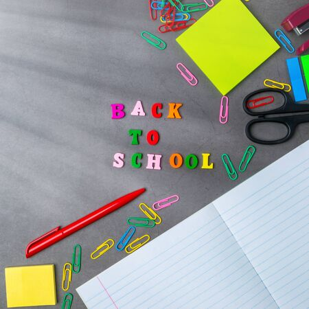 The layout of school supplies on a dark gray background. Top view, the suns rays from the side. Back to school. Flat lay