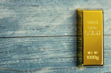 Ingot of pure gold metal bullion on a background of blue wooden boards