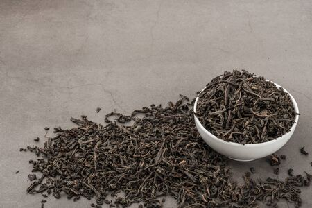 Dried tea is poured into a white ceramic cup on a gray textured background