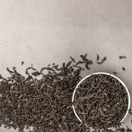 Dried tea is poured into a white ceramic cup on a gray textured background. View from above. Layout Stok Fotoğraf