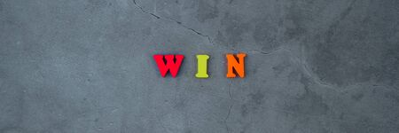 The multicolored win word is made of wooden letters on a grey plastered wall background Banque d'images - 129313612