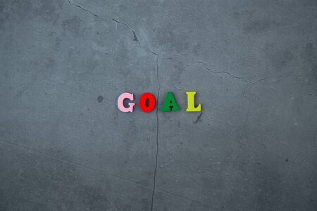 The multicolored goal word is made of wooden letters on a grey plastered wall background Banque d'images - 129313871