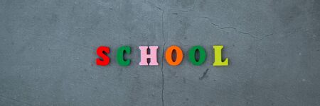 The multicolored school word is made of wooden letters on a grey plastered wall background