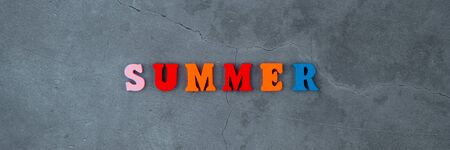 The multicolored summer word is made of wooden letters on a grey plastered wall background Banque d'images - 129314261