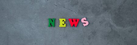 The multicolored news word is made of wooden letters on a grey plastered wall background. Banque d'images - 130592306