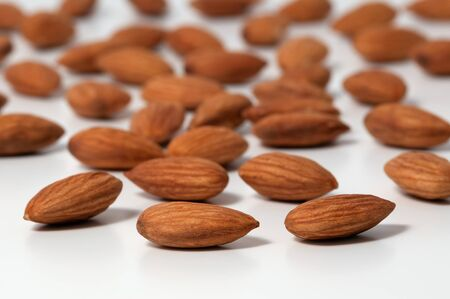 Almond nut scattered on a white background close-up 스톡 콘텐츠