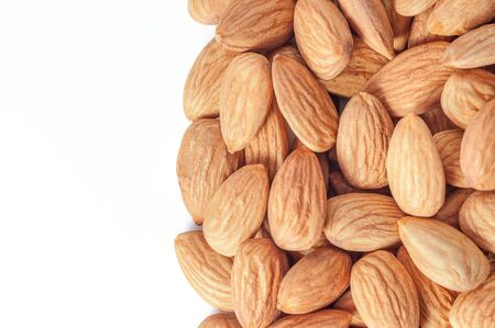 Almond nut close-up, white background, place for inscription.