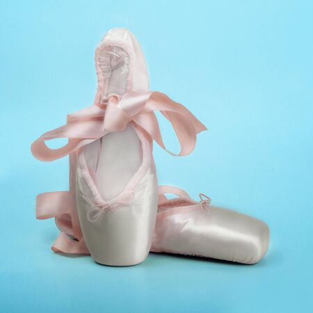 Pointe shoes ballet dance shoes with a bow of ribbons beautifully folded on a blue background
