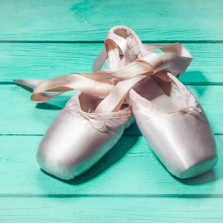 Pointe shoes ballet dance shoes with a bow of ribbons beautifully folded on a wooden background