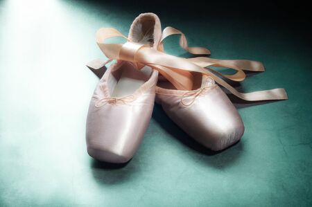 Pointe shoes ballet dance shoes with a bow of ribbons beautifully folded on a green background