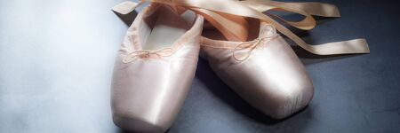 Pointe shoes ballet dance shoes with a bow of ribbons beautifully folded on a dark background