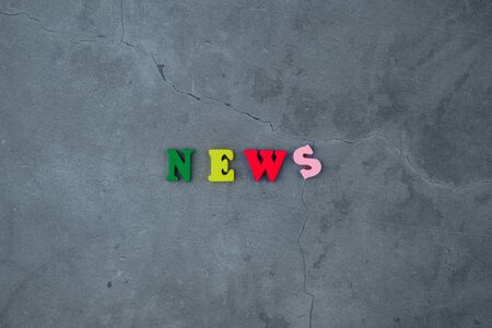 The multicolored news word is made of wooden letters on a grey plastered wall background. Banque d'images - 131337377