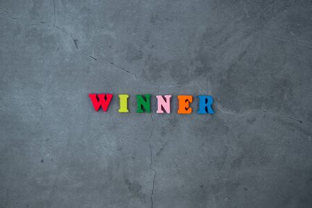 The multicolored winner word is made of wooden letters on a grey plastered wall background. Banque d'images - 131337378