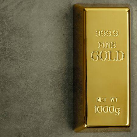 Ingot of pure gold metal bullion on a gray textured background. Stock Photo