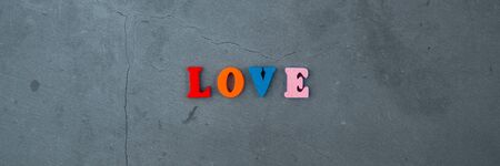 The multicolored love word is made of wooden letters on a grey plastered wall background Banque d'images - 131337420