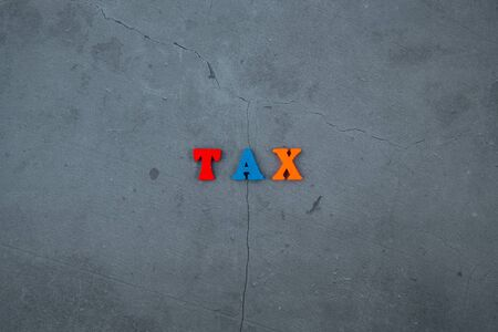 The multicolored tax word is made of wooden letters on a grey plastered wall background Banque d'images - 131337418