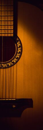 Acoustic guitar close-up in the dark, illuminated by a beam of light