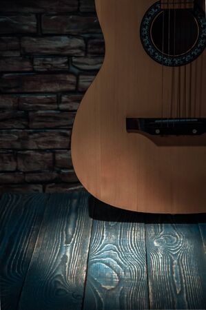 Acoustic guitar standing at the brick wall illuminated by a beam of light. Light spot on the floor boards Stock Photo