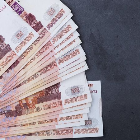 Big stack of Russian money banknotes of five thousand rubles lying on a grey cement background
