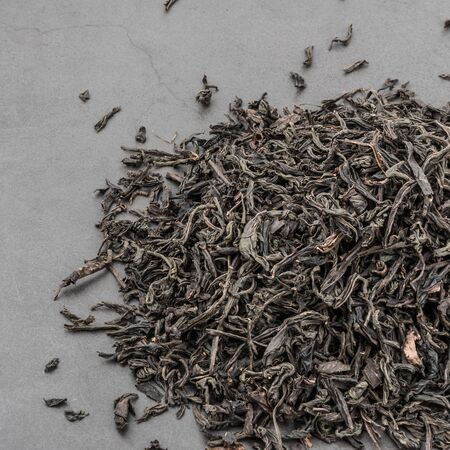 Dried tea is poured scattered on a grey textured background
