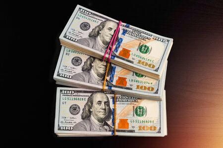 Three packs of one hundred dollar cash bills on a dark table. Lighting on the side. Stock Photo