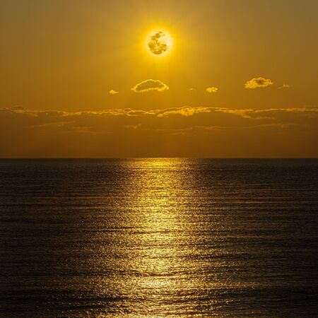 The moon and clouds in the golden sky above the ocean horizon at midnight, moonlight is reflected in the ribbed surface of the water. Night landscape, background of the night sea Stok Fotoğraf