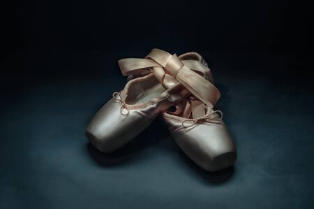 Pointe shoes ballet dance shoes with a bow of ribbons beautifully folded on a dark background Foto de archivo - 139504744