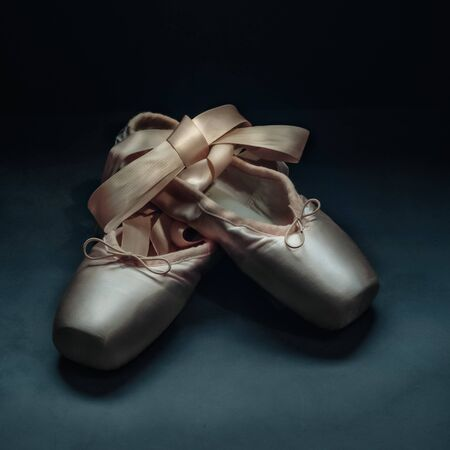 Pointe shoes ballet dance shoes with a bow of ribbons beautifully folded on a dark background Foto de archivo - 139504543