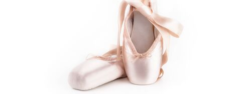 Pointe shoes ballet dance shoes with a bow of ribbons beautifully folded on a white background with a lot of light Foto de archivo - 139504865