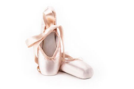 Pointe shoes ballet dance shoes with a bow of ribbons beautifully folded on a white background with a lot of light Foto de archivo - 139504614