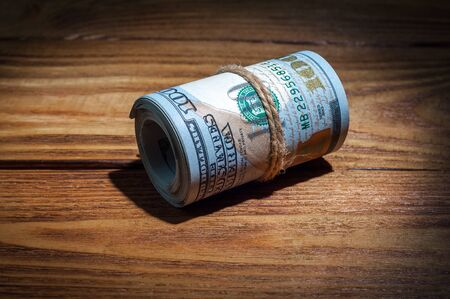 A roll of dollars on a wooden textured table in the dark illuminated by a ray of light