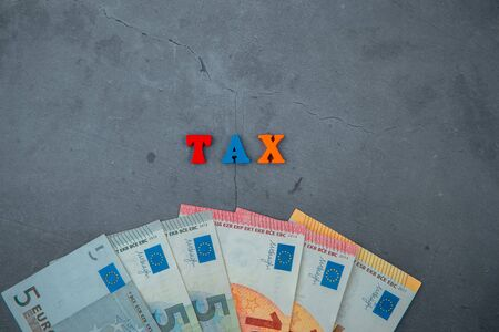 The multicolored tax word is made of wooden letters on a grey plastered wall background Banque d'images - 140990755