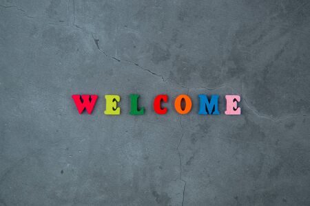 The multicolored welcome word is made of wooden letters on a grey plastered wall background