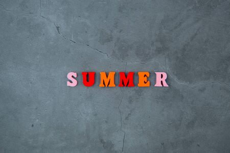 The multicolored summer word is made of wooden letters on a grey plastered wall background Banque d'images - 140990722