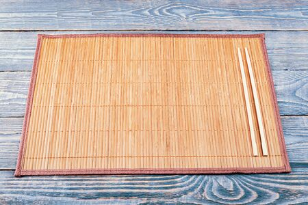 Two wooden chopsticks lie on the edge of a bamboo Mat that sits on a wooden table made of textured boards. Archivio Fotografico - 142190764