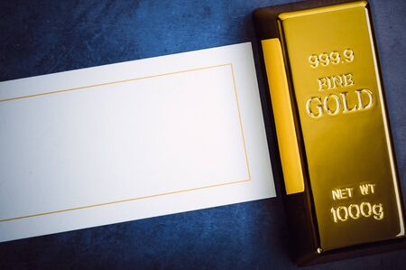 An ingot of gold metal bullion of pure brilliant diagonally located on a blue textured background