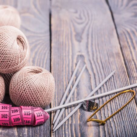 Balls of yarn, knitting needles and measuring tape on a wooden background