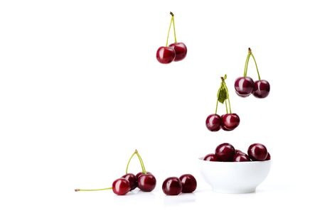 Ripe red cherries with green sticks and leaves fall into a white ceramic bowl overflow it and scatter around it on a white isolated background.
