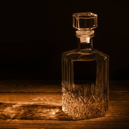 An elegant empty carafe, on a textured wooden table. Decanter in dark style